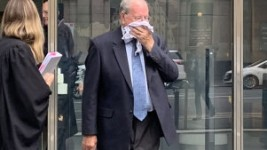 Paedophile priest Rex Francis Elmer tried to hide his face after pleading guilty in the County Court in Melbourne on Monday.