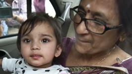 One-year-old Aishwarya Bhattacharya is held by her grandmother in a car shortly after her arrival at IGI airport in New Delhi, India, a year after Norwegian officials took her away.